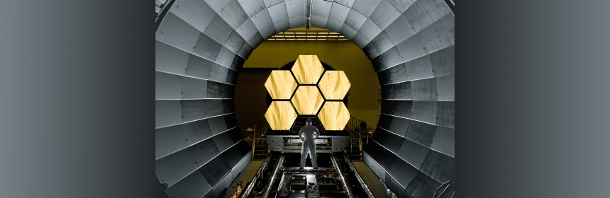 A worker at NASA inspects part of the James Webb Space Telescope.